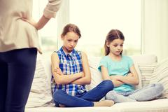 upset guilty little girls sitting on sofa at home - stock photo
