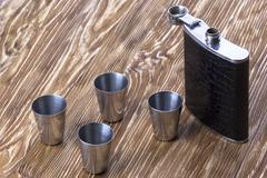 Metal flask trimmed leather and four metallic, sturdy shot glasses. - stock photo