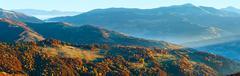 Sunbeam and autumn misty mountain panorama. - stock photo