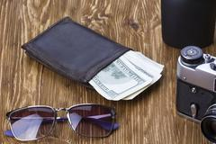 Gentlemanly set:  sunglasses, perfume, wallet, money,camera on wooden background Stock Photos