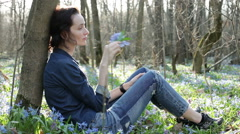 The young woman smelling the bouquet of the bluebells - stock footage