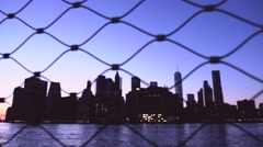 Dolly out shot of Manhattan skyline behind the fence at sunset Stock Footage