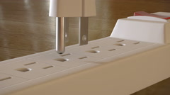 A grounded electric plug with  prongs is inserted into an outlet strip Stock Footage