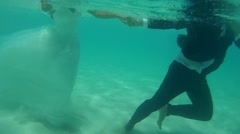 UNDERWATER: The bride and groom are on the sandy bottom. Stock Footage
