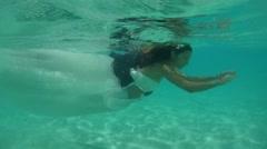 UNDERWATER: The bride and groom are floating underwater. Stock Footage