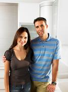 Couple standing in kitchen smiling Stock Photos