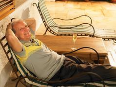 Senior Adult man lying on sun lounger - stock photo
