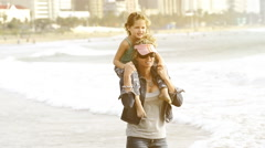 Mother and daughter on beach in the early morning. Young girl sitting on moth - stock footage