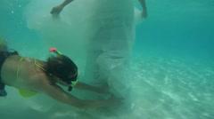 UNDERWATER: Assistant bride prepares for underwater shooting. Stock Footage