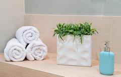 Stock Photo of Stack of towels with a soap dispenser in a bathroom
