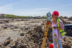 Female geodesist is working with total station on a building site. Stock Photos