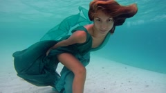 Stock Video Footage of UNDERWATER: Young beautiful girl in dress posing submerged under water.