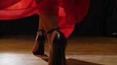 Female model in heels walking on hardwood floor in red dress Stock Footage
