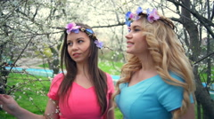 Two girls wearing circlets of flowers posing in spring blossom park slow motion Stock Footage