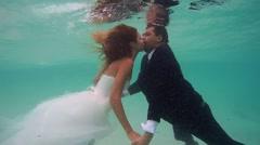 UNDERWATER: Bride and groom kissing under water. - stock footage
