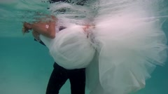 UNDERWATER: The groom holds a bride. Stock Footage