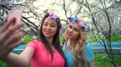 Two girls wearing circlets of flowers making selfie in spring blossom park Stock Footage