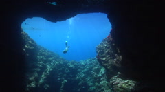 Ocean scenery free diver swims into mariners cave and surfaces inside, shot from Stock Footage