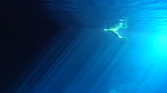 Ocean scenery free diver dives and ascends through sun rays in swallows cave, Stock Footage