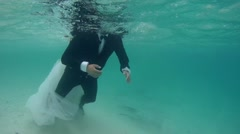 UNDERWATER: Bride ride on the back of the bride. Stock Footage