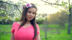 Young female wearing circlet of flowers posing in spring blossom slow motion Stock Footage