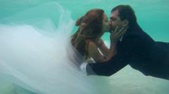 UNDERWATER: Bride and groom kissing under water. Stock Footage