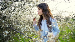 Beautiful young woman tastes the flavour of blooming tree slow motion Stock Footage