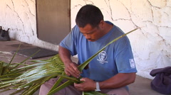 Tongan man weaving palm leaves, looks up and smiles at the camera, people or Stock Footage