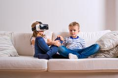 Boy and girl wearing virtual reality goggles. Studio shot Stock Photos