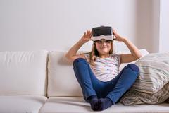 Girl wearing virtual reality goggles. Studio shot, white couch - stock photo