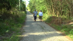 Tourists walking along deserted road, people or person in shot, HD, UP15764 - stock footage
