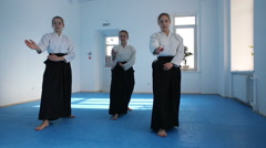 Three girls in black hakama practice Aikido movements on martial arts training Stock Footage