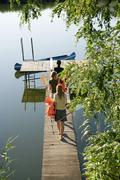 Three young women on a pier with oars. - stock photo