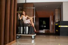 Woman on luggage trolley being pushed Stock Photos