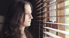 Young woman looking out window through blinds Stock Footage