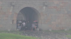 People hide from the rain in Hwaseong fortress in Suwon, Korea. Stock Footage