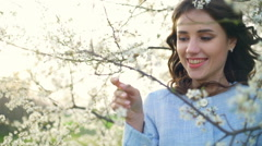Beautiful young female amidst the spring tree blossom slow motion Stock Footage