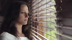 Young woman peers through blinds out a window Stock Footage