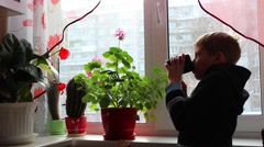 Child drinking tea and looking out of the window Stock Footage