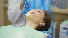 Dentist cleans patient's face with air blow Stock Footage