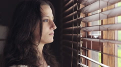Girl peers out window through curtain blinds Stock Footage