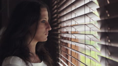 Girl opens blinds and looks out of window Stock Footage