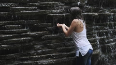 Girl drinking from trickling waterfall Stock Footage