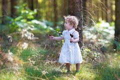 Beautiful little baby girl walking in a sunny autumn park wearing a white dress Stock Photos