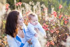 Portrait of a young beautiful mother and her new born baby in an autumn park Stock Photos