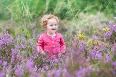 Beautiful little baby girl walking in purple autumn flowers in a heath landscape Stock Photos