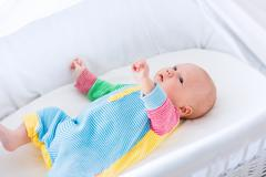 Cute baby boy in a white crib - stock photo