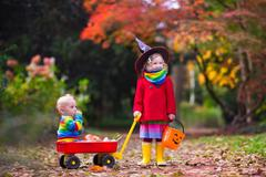 Kids trick or treat at Halloween - stock photo
