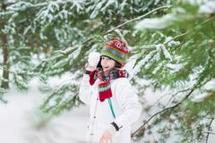 Funny cute boy playing snow ball in a snowy winter park in his Christmas holiday Stock Photos