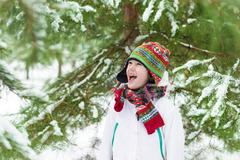 Funny little boy screaming of joy playing snow ball fight in a snow park - stock photo